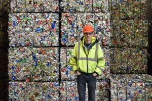 Brian Dubis, operations supervisor at the MRF, stands in front of finished bales of sorted recycling. (Credit: Vin Sowders)