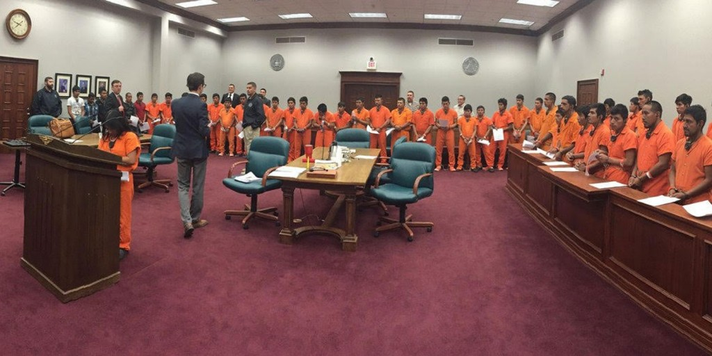 "A recently leaked image shows dozens of immigrants in orange jumpsuits, their hands and feet shackled, undergoing a ""mass trial"" in Pecos, Texas, a small town roughly 70 miles southwest of Odessa. (Source: The Intecept via The Houston Chronicle)"