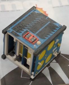 Brown University EQUiSAT true-scale mock-up model, 10cm cube, shown against Motif Magazine cover for scale. Black areas show position of solar cells. (Photo: Michael Bilow)